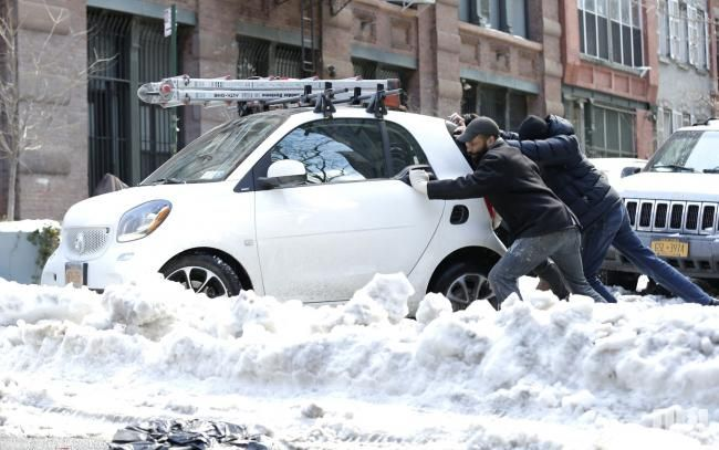 Three Men Push A Smart Car Pion Coupe Out Of The Snow And Into Street In New York City On March 16 2017 Clean Up Continues 2 Days