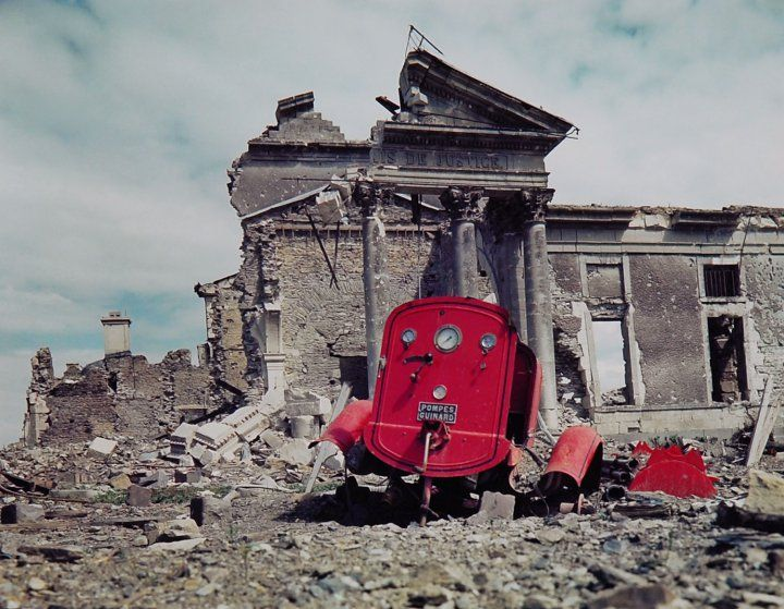 View of the ruins of the Palais de Justice in the town of St. Lo, France, summer 1944. The red metal frame in the foreground is what's left of an obliterated fire engine.