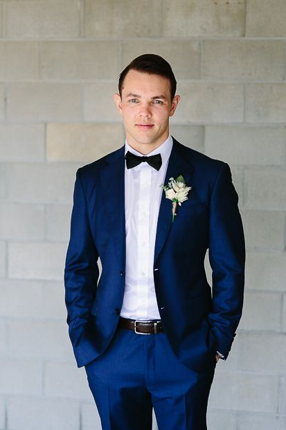 Handsome groom in blue suit with bow