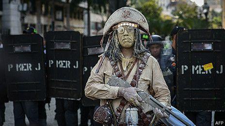En esta imagen del 1º de octubre se observa a un manifestante contra la corrupción  en Río de Janeiro que lleva un rifle falso.