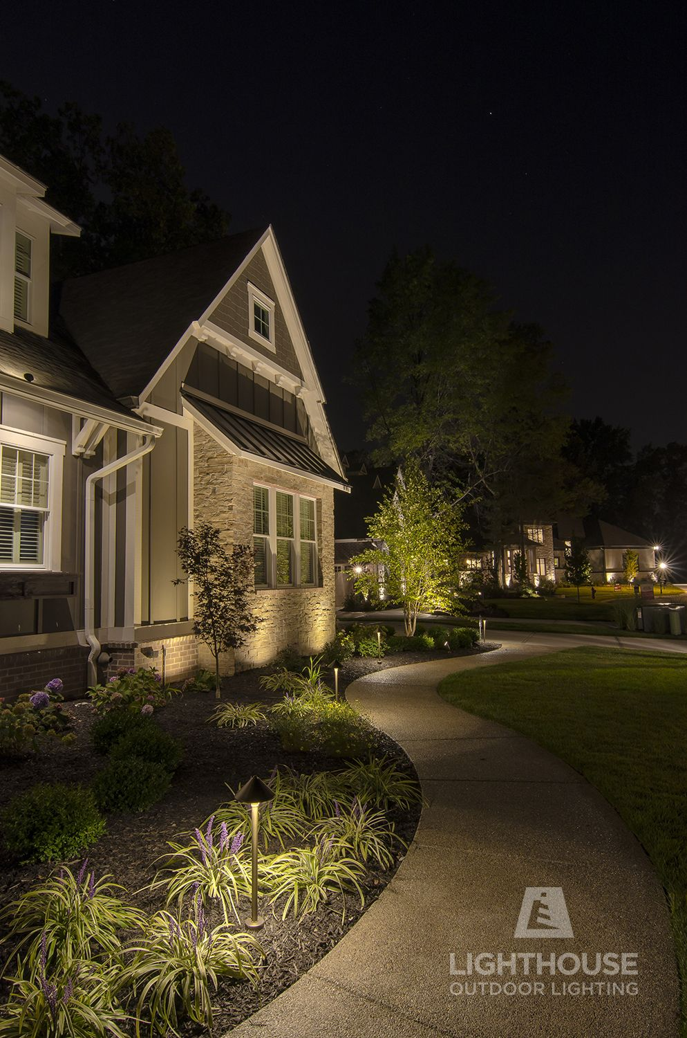 lighthouse outdoor lighting path lights illuminate the walkway in front of this home landscape lighting designed and installed by lighthouse outdoor lighting indianapolis