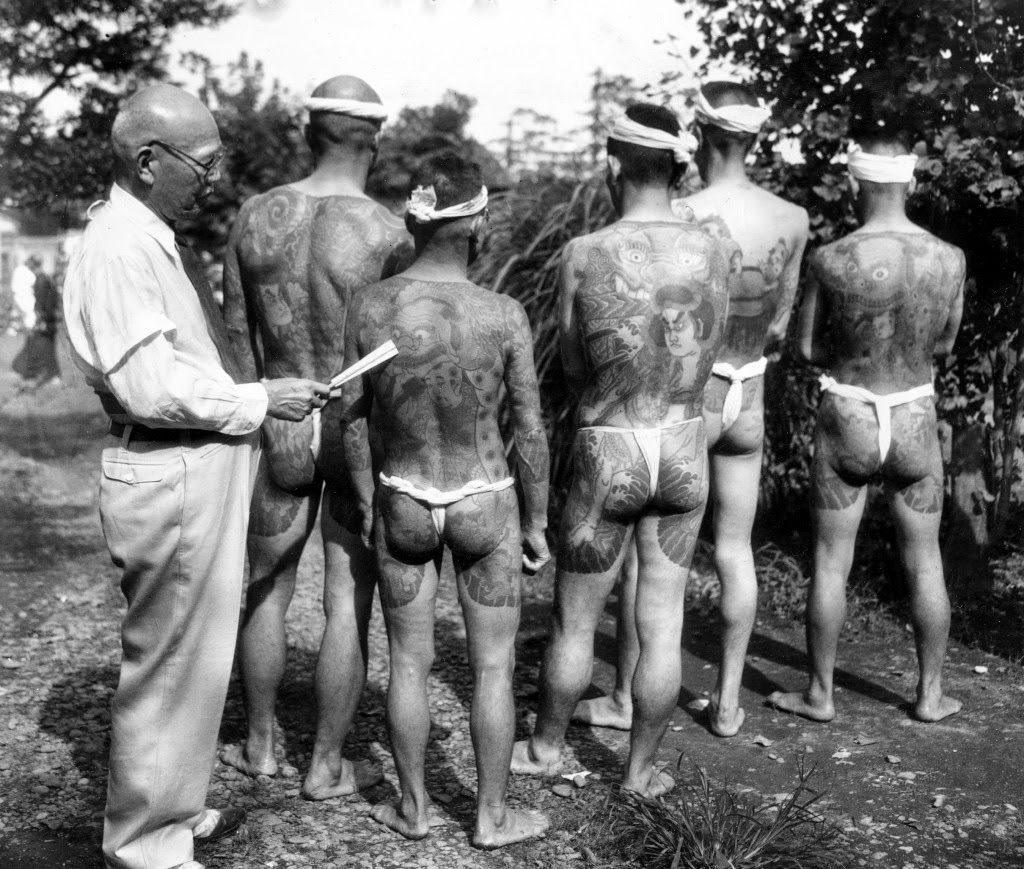 Japanese tattoo artist Ginjiro Susuki, 72, left, exhibits some of his tattoo designs at the Hard Skin Club convention of tattooed men and women held in Tokyo, Japan, Sept. 2, 1948. Suzuki estimates that he has tattooed more than 10,000 persons in his lifetime devotion to the 300-year-old art. (AP Photo)