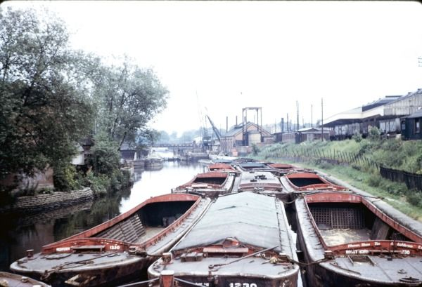 """BW197-2-8-38-1 Brentford including moored lighters, the construction of a new lock alongside an existing lock, the lockkeeper Jack Barlow and narrowboats including the butty """"Kew"""" at Brentford depot. Date nd [1950s]"""