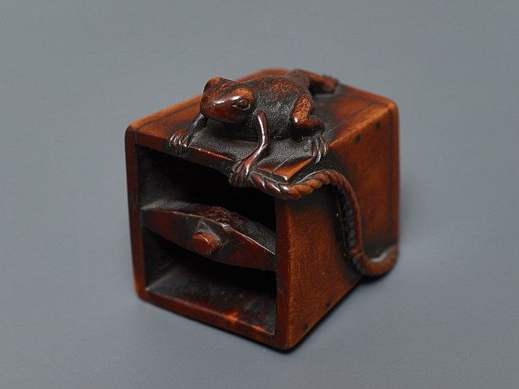 Netsuke, wood. Japan, 19th cent.Skillful realistic depiction with very beautiful, deep red-brown color of the wood. The bucket is four-sided and wider to the top, a cross stick is attached over the opening on which a rope was tied for drawing water from a well. The rope is broken off, seen coiling around one side. On the other, a frog is crawling in lively naturalistic composition. More rows of pegs in black horn are inlaid. The cord passage is in the middle of the fourth side, which is not…