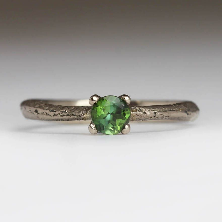 This ring is made by casting recycled 18ct white gold in beach sand, which creates the texture you see on the band. Set with a 4mm green tourmaline in an …