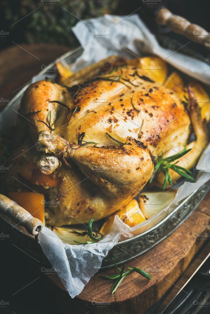 #Roasted whole chicken  Close-up of Christmas roasted whole chicken stuffed with oranges bulgur and rosemary in vintage metal tray over rustic wooden board background. Selective focus Slow food concept