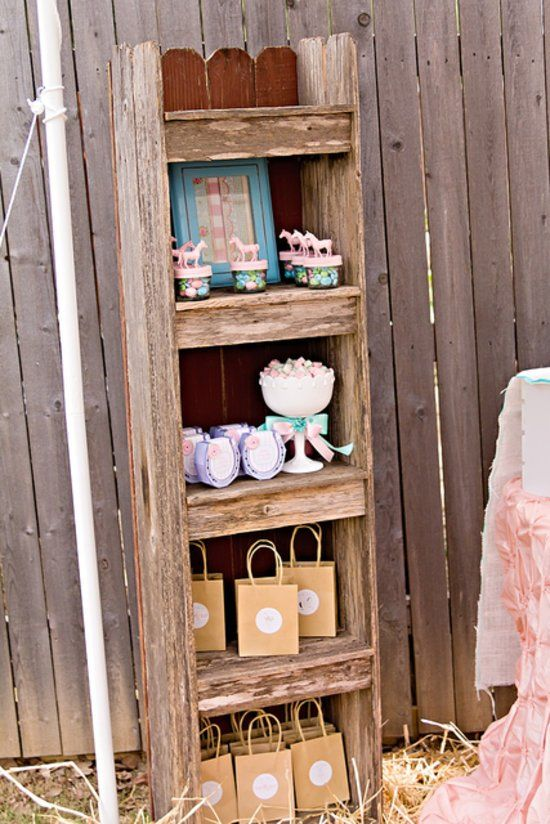 """Rustic Wooden Bookshelves For a Pony Party: """"I found a rustic wooden bookshelf on Craigslist and used it as my thank-you-gift station,"""" says Miranda Konieczny of Whimsically Detailed, who planned this pretty pony party for her daughter. """"There was Sensa-Dough, chocolate horses, bubbles, and lots of treats!"""" """"I purchased mini plastic horses and hot-glued them to tops of mason jars and then spray-painted them pink. Each container had a little bit of sweet for each child to go home with. Also…"""