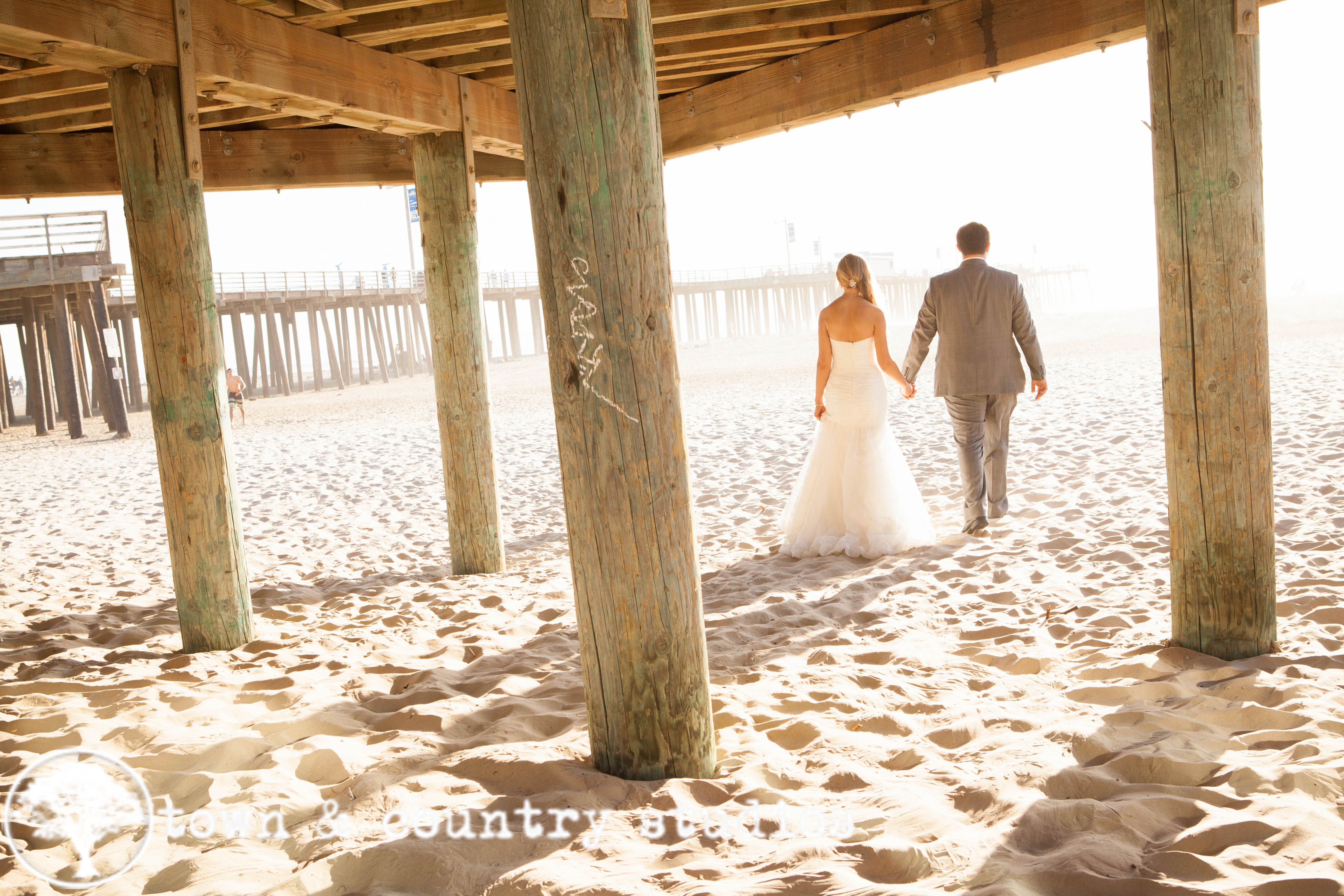 Beach wedding sand ceremony sets  Walking away from the pier hand in hand  Our Beach Wedding Images
