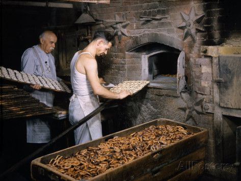 Men Load Trays Of Pretzels Into A Bakerys Old Fashioned Oven