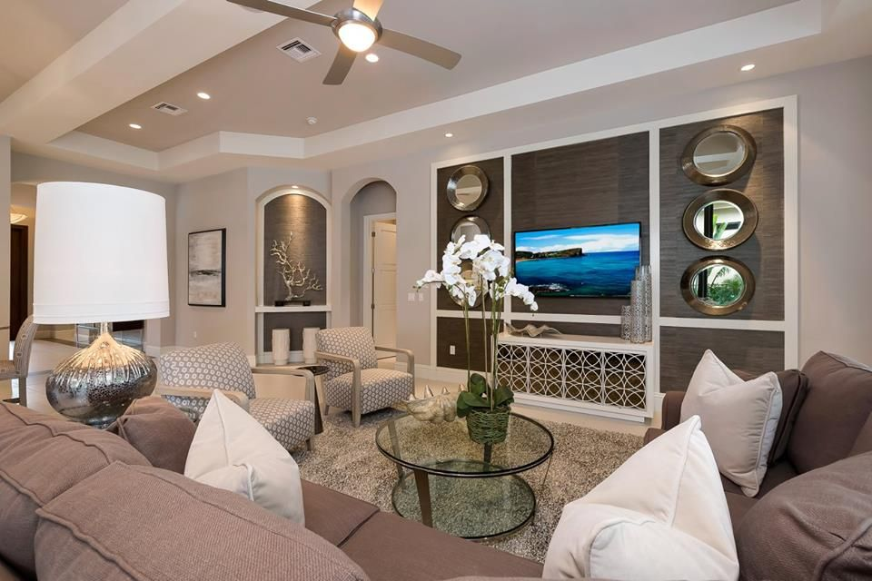 Note this media wall design. Can frame out wall and use upholstered sections as backdrop for flat screen tv and white painted furniture to house media equipment. Like the round mirrors hung in series for reflection of light - round shape echoes idea of porthole. can also use series of indigo coral/sea shell prints hung in white frames down each side. Cipriani_Living_Room