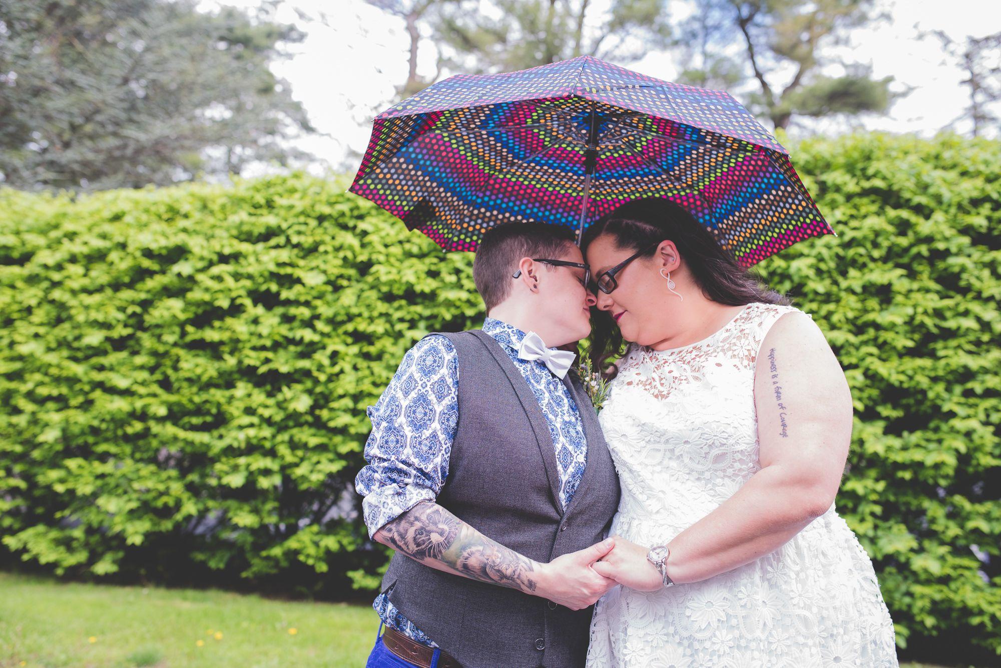 Cheri + Rachel's Same Sex Morris Museum Wedding || New Jersey Weddings || BG Productions Photography || www.bgproonline.com #rainydaywedding #rainbowumbrella #photoswithumbrellas #staydryweddingphotos