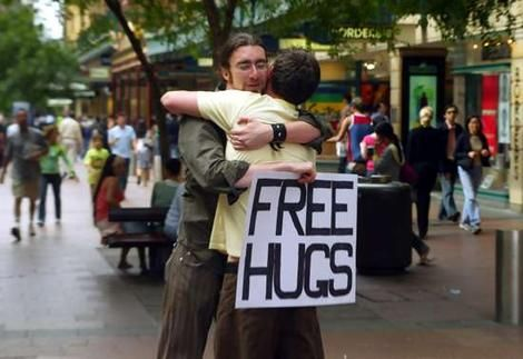 """Juan Mann, the creator of the free hugs phenomenon created it after he """"had been feeling depressed and lonely as a result of numerous personal difficulties. However, a random hug from a stranger made an enormous difference.After being asked to stop campaigning for hugs, he befriended the lead singer from the Sick Puppies who featured him in his """"all the same"""" video creating the phenomenon"""