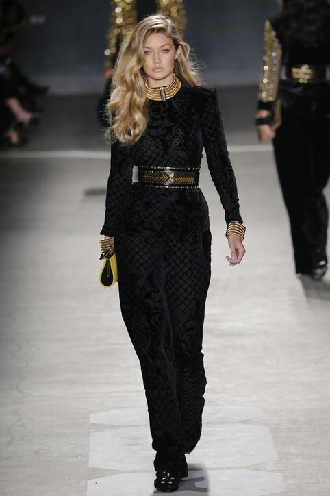 Gigi Hadid on the runway for Balmain x H&M in a black jumpsuit and belt