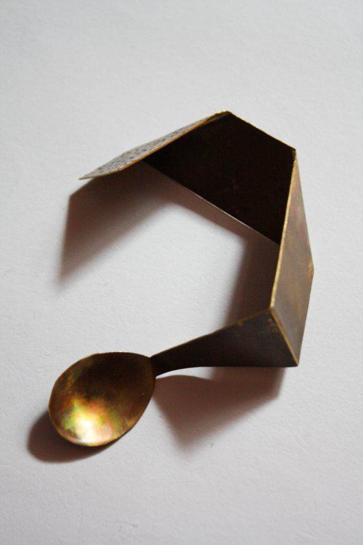 Folded brass spoon
