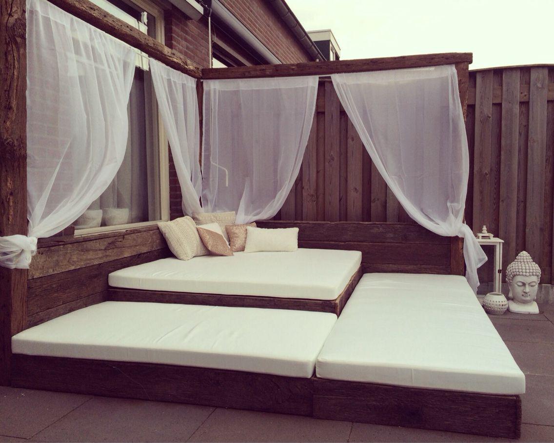 Ligbed van houten wagon planken loungebed met witte kussens