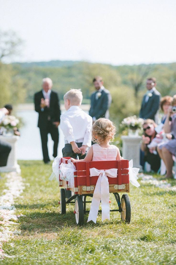 Ring bearer pulling the flower girl down the aisle in a red wagon