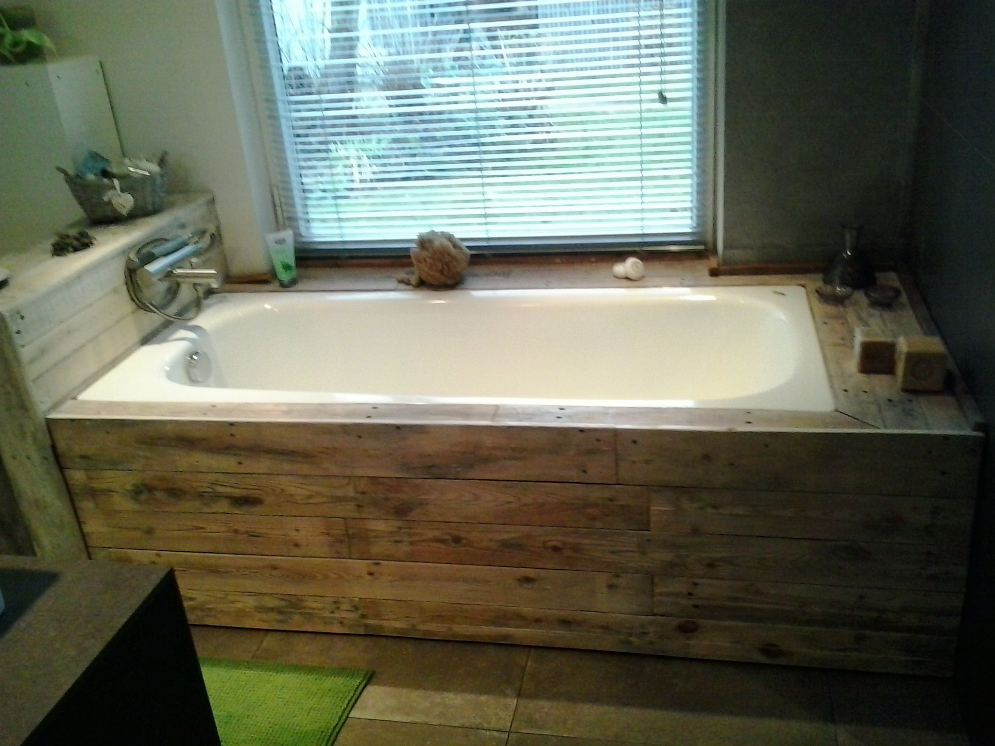 Palletwood used for incasing bathtub. fosset fixed on low wall used ...