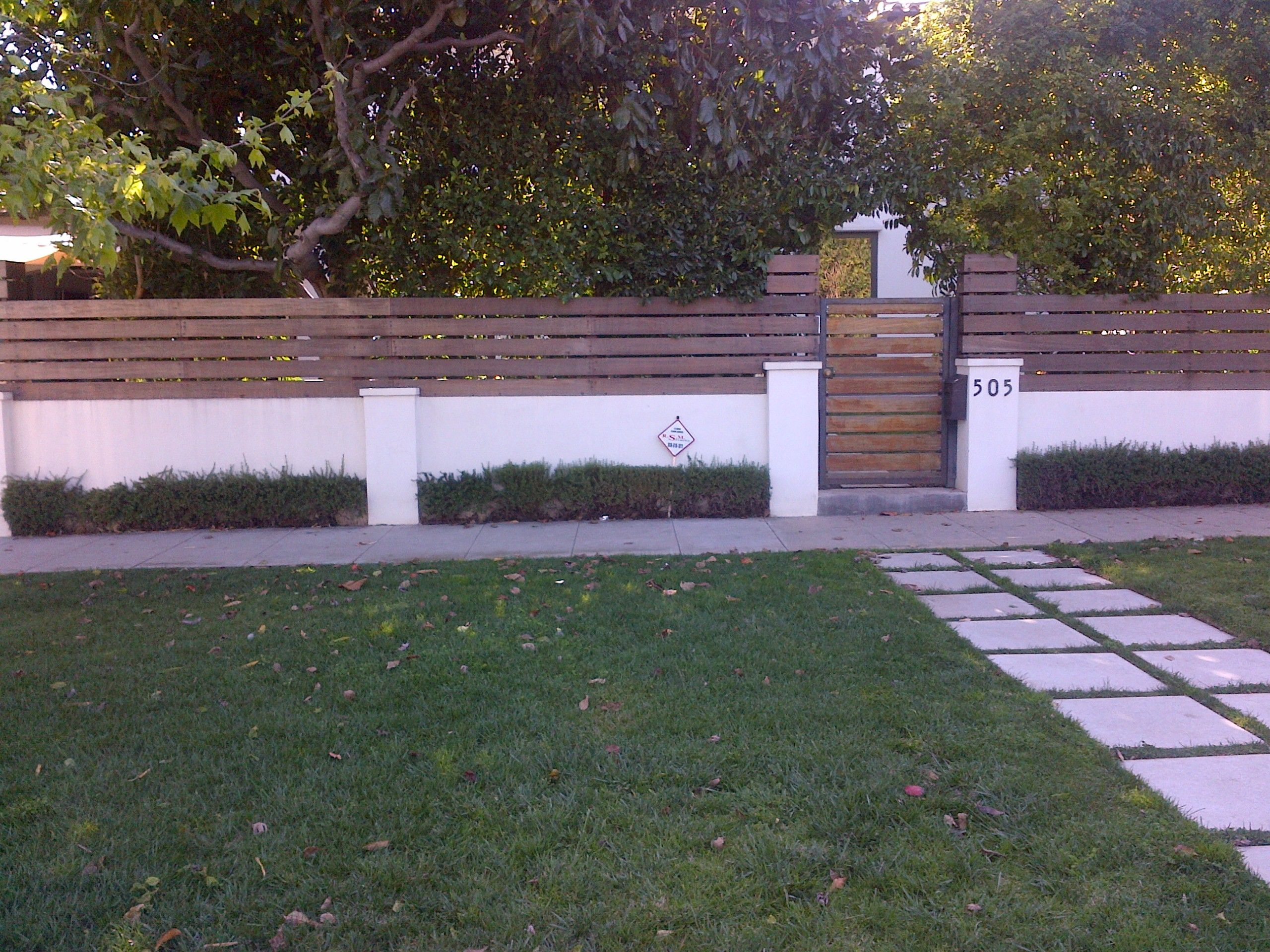 Wood and stucco wall just add lush tropical landscaping for Stucco garden wall designs