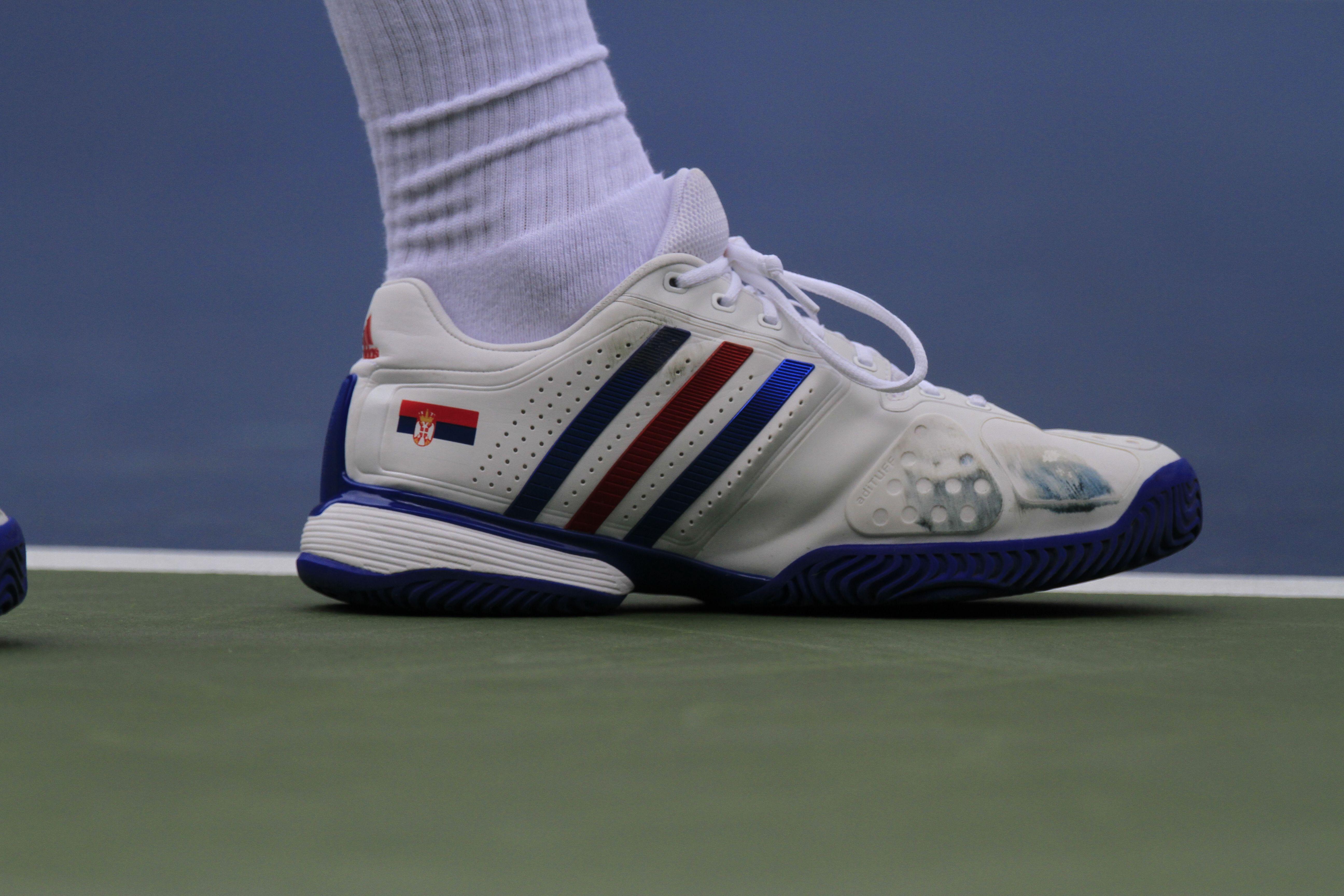 Novak Djokovic sports white shoes with the Serbian flag