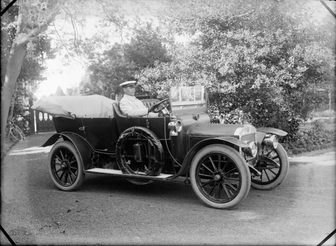 Unidentified chauffeur in a motorcar, on a driveway, showing trees and bicycle leaning on a tree, probably Christchurch district