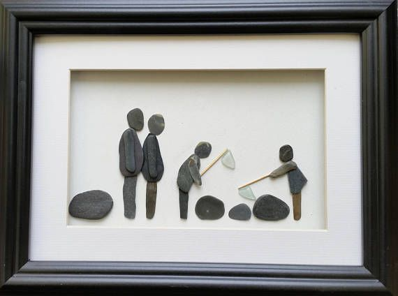 A family of four spending time together rock pooling on the beach - complete with nets and bucket. This pebble picture is set inside a a 26cm x 35cm glazed box frame that is available in either black or white.