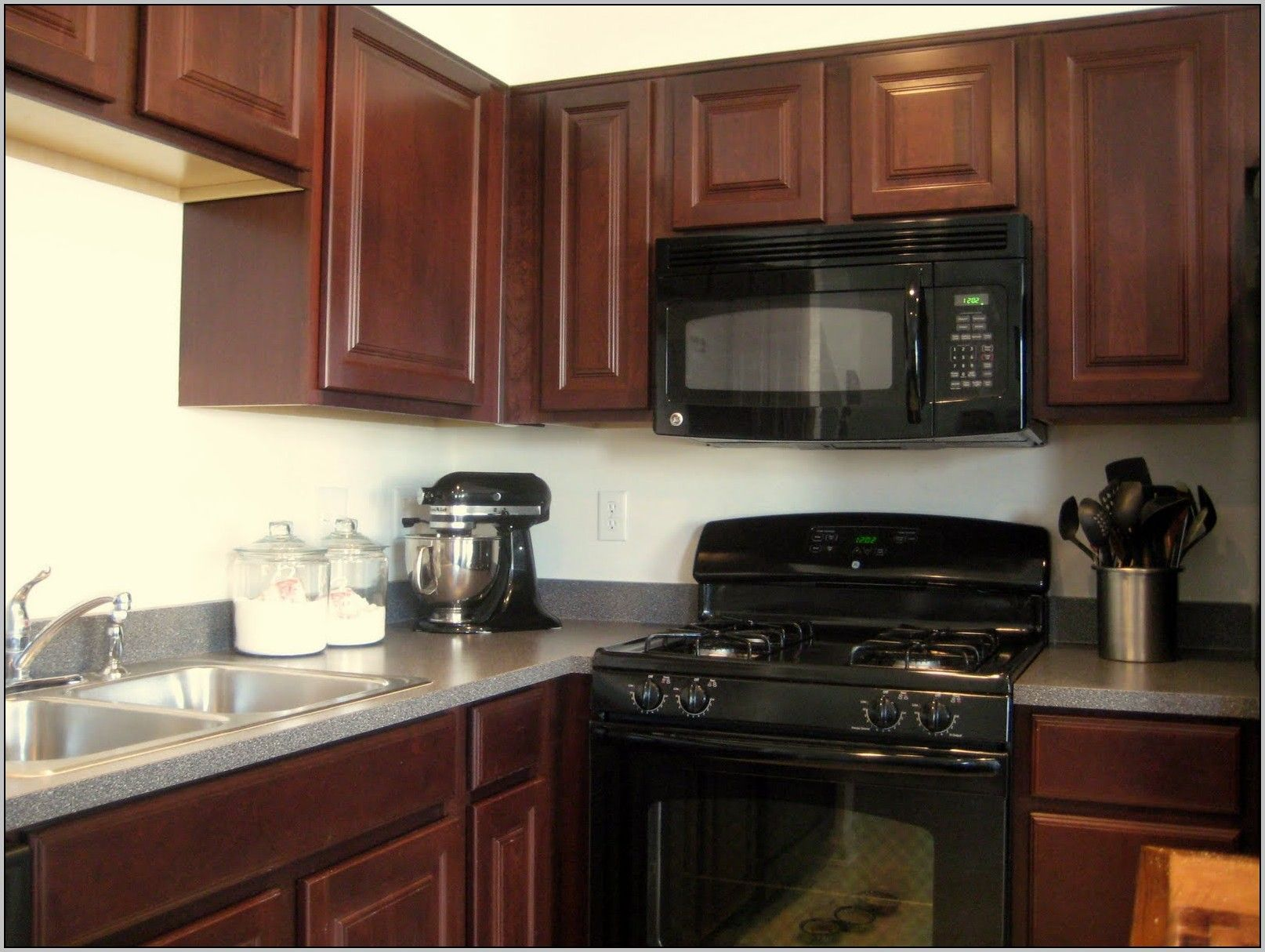 Here Are The Best Kitchen Paint Colors According To Top Designers Kitchen Cabinets With Black Appliances Dark Brown Kitchen Cabinets Brown Kitchen Cabinets