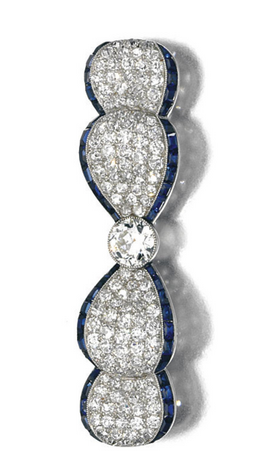 SAPPHIRE AND DIAMOND BROOCH, 1920S Designed as a bow, the borders set with calibré-cut sapphires, millegrain-set with circular and single-cut diamonds.