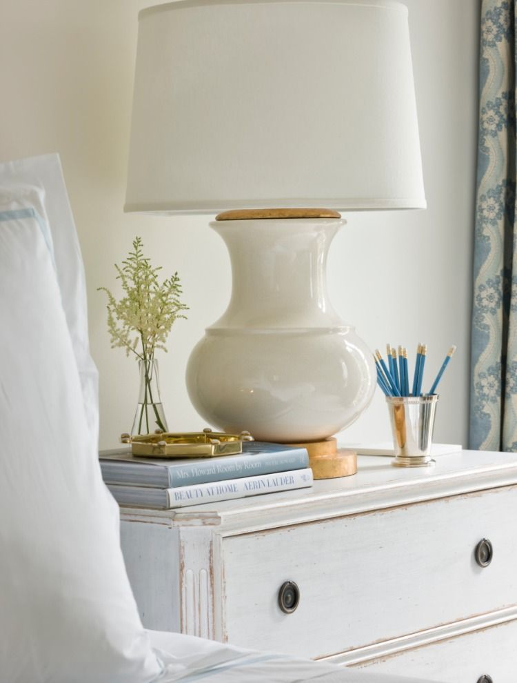 Gorgeous white lamp and nightstand in classic country bedroom. House ...