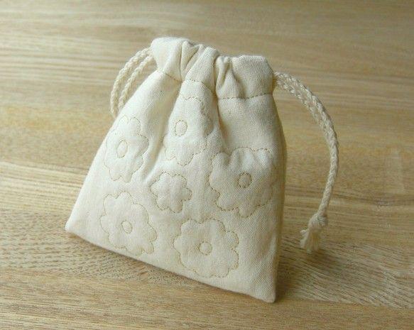やわらかな花キルトのミニ巾着袋です。ミシンステッチで花模様を表地両面にあしらいました。キルト芯を挟んでいますのでクッション性があります。アクセサリー入れや香り...|ハンドメイド、手作り、手仕事品の通販・販売・購入ならCreema。
