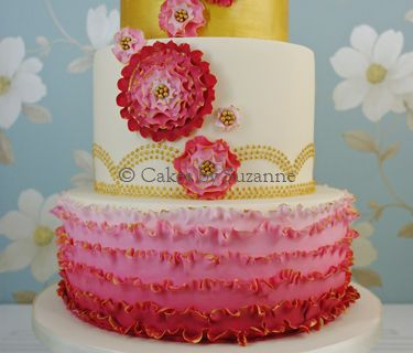 Ombre ruffle cake, with graduating shades of pink/red ruffles accented with edible gold paint on the bottom tier, gold piped dots on the extra tall middle tier and a plain gold top tier.