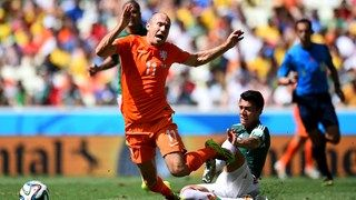 Arjen Robben of the Netherlands is tackled by Hector Moreno of Mexico