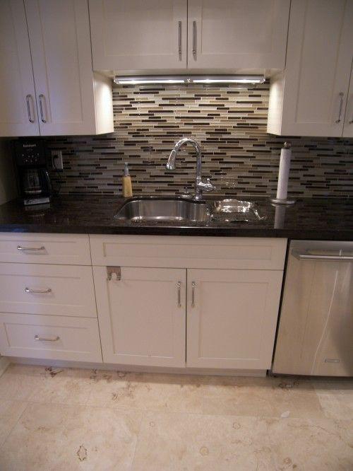 White cabinets, black countertop, backsplash brings beige floor ...