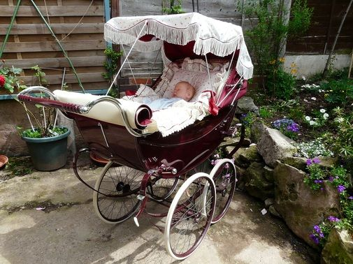 Baby in his pram outside getting fresh air with a sun canopy to protect him from the sun, I used to do this with my boys in 80's it's such a shame people don't use prams nowadays so much and most don't use a sunshade :(