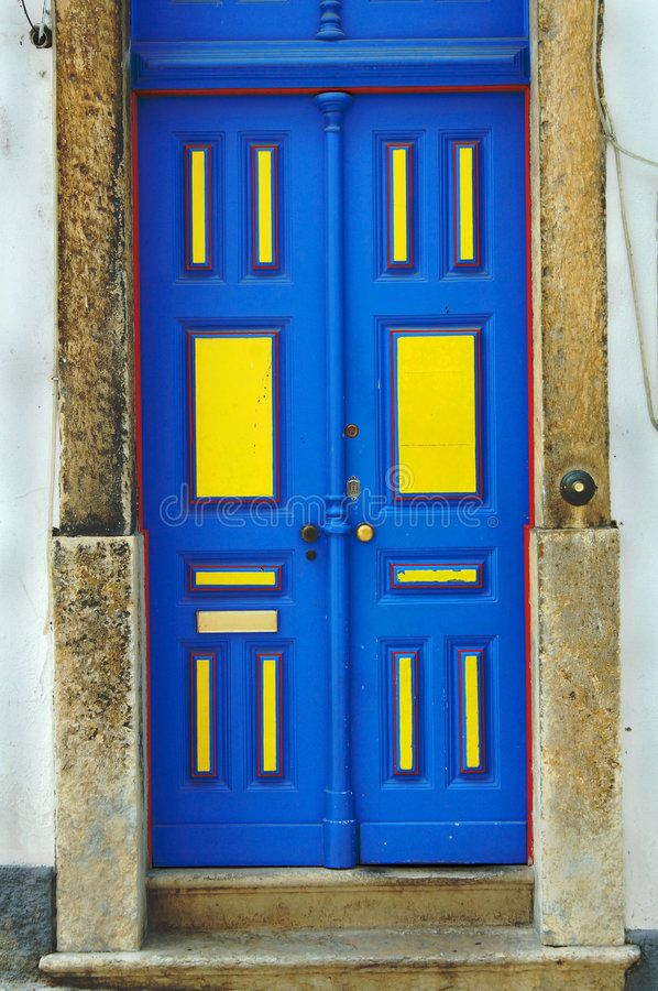 Blue Door. Closed wooden door with bright blue and yellow colors on wall ,
