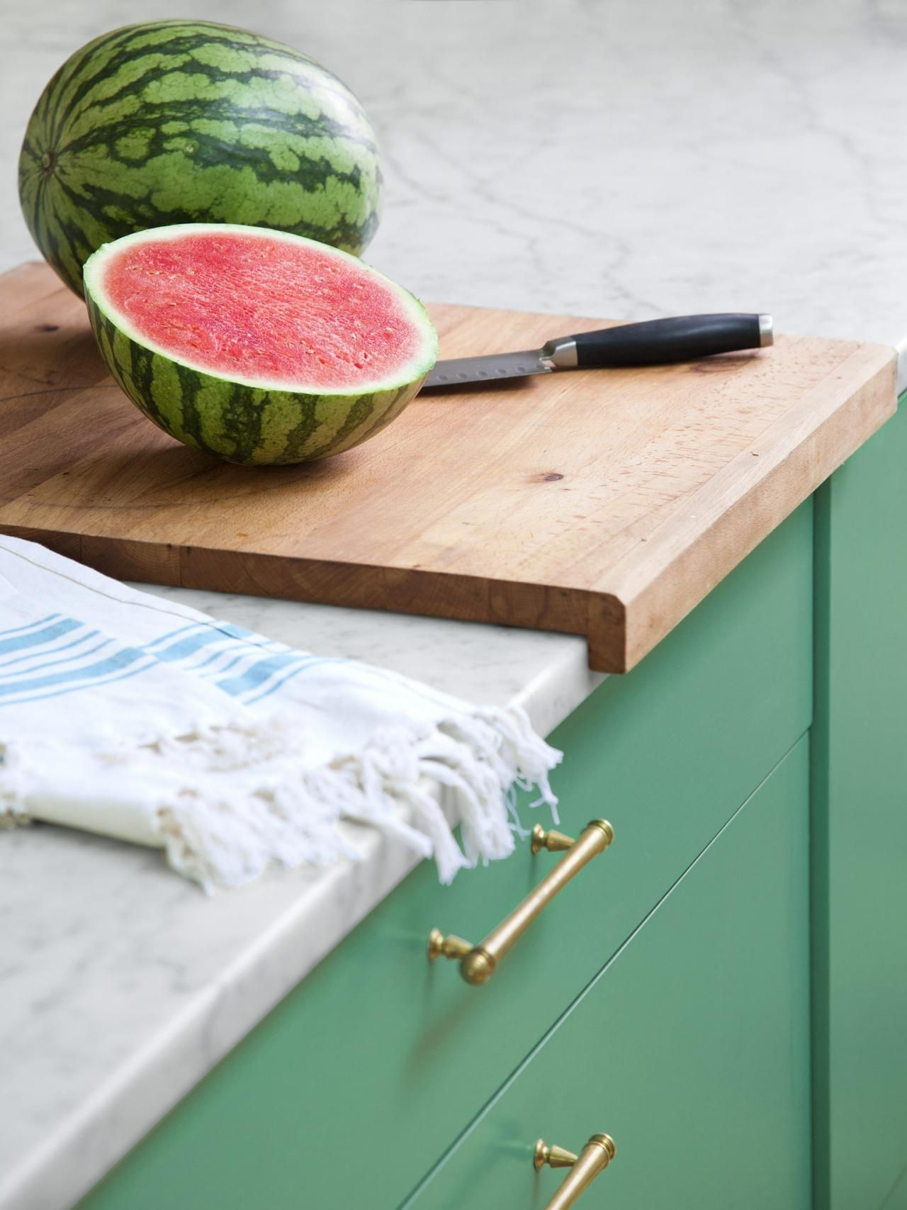A notched ikea cutting board stays in place on the counter