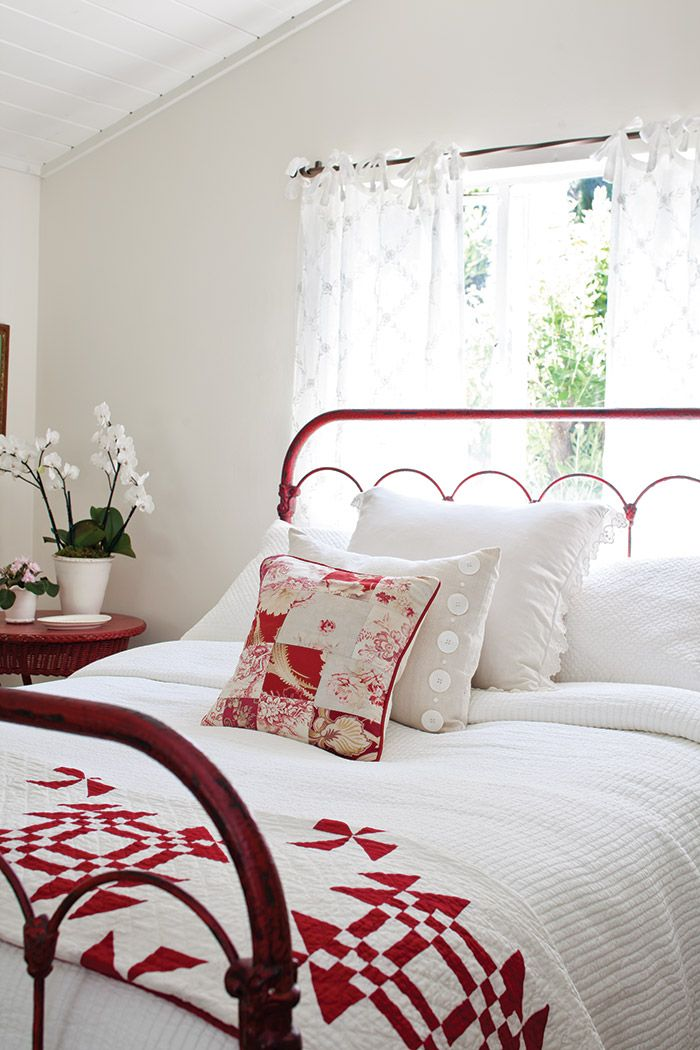 white bedroom with red metal bed frame and quilt at the foot of the ...