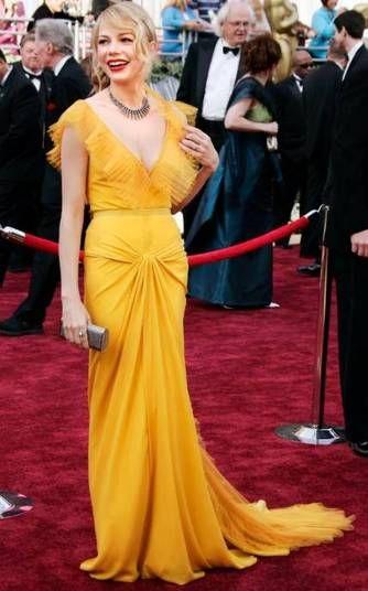 Michelle Williams encarou com desenvoltura o look amarelo ouro de Vera Wang no Oscar 2006, que fez um par perfeito com sua pele de porcelana