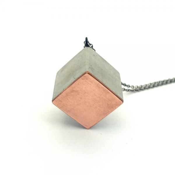 One size cube necklace in a minimalist Nordic design, made from stone cast to give it a soft a smooth feel and the aestetics of industrial concrete and cement. Together with an embedded piece of cobber, this necklace really stands out. Note that surface and appearance might vary from the image as all of our jewellery are handmade.  Silver-oxidized chain. Chain length approx. 75 cm - please ask for other lenghts. ----- About the designer: In our first line of jewellery, we seek to break with…