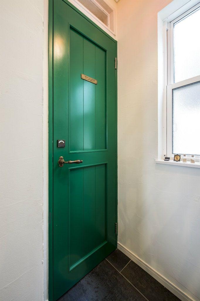 トイレの造作ドア 瑠璃色タイルが美しい レトロモダンな家 トイレ