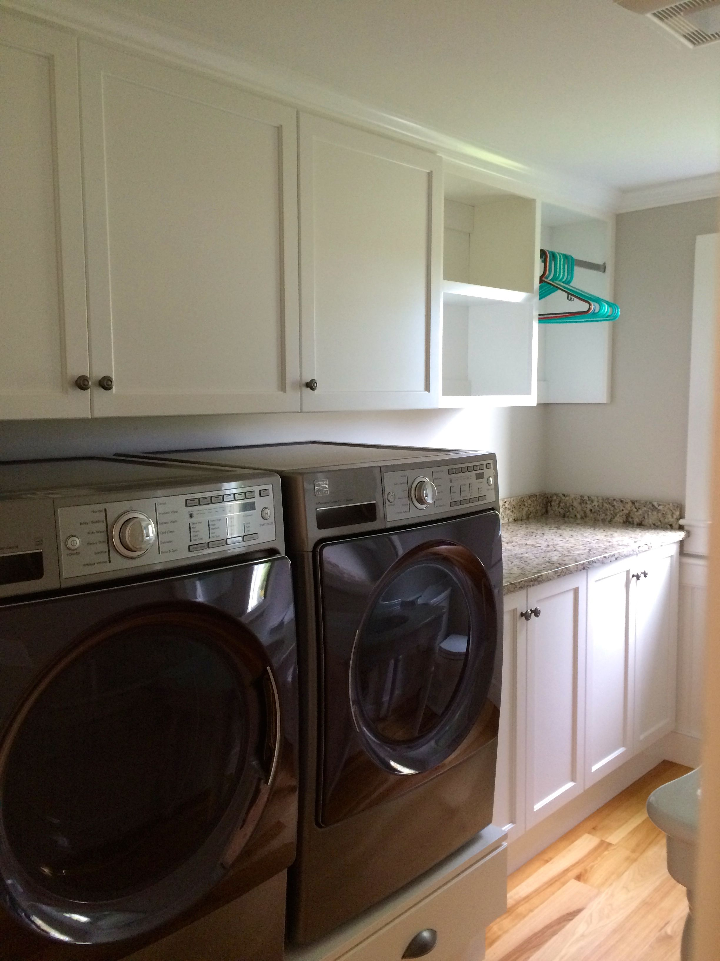 A Well Organized Laundry Room With Cabinetry, Open Shelving, A