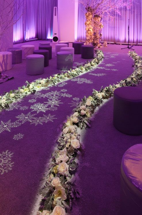 Transform our space with uplighting and beautiful flower aisle flower lined and snowflake light creates an icy glow for this winter wedding venue with purple and lavender seating stools junglespirit Gallery