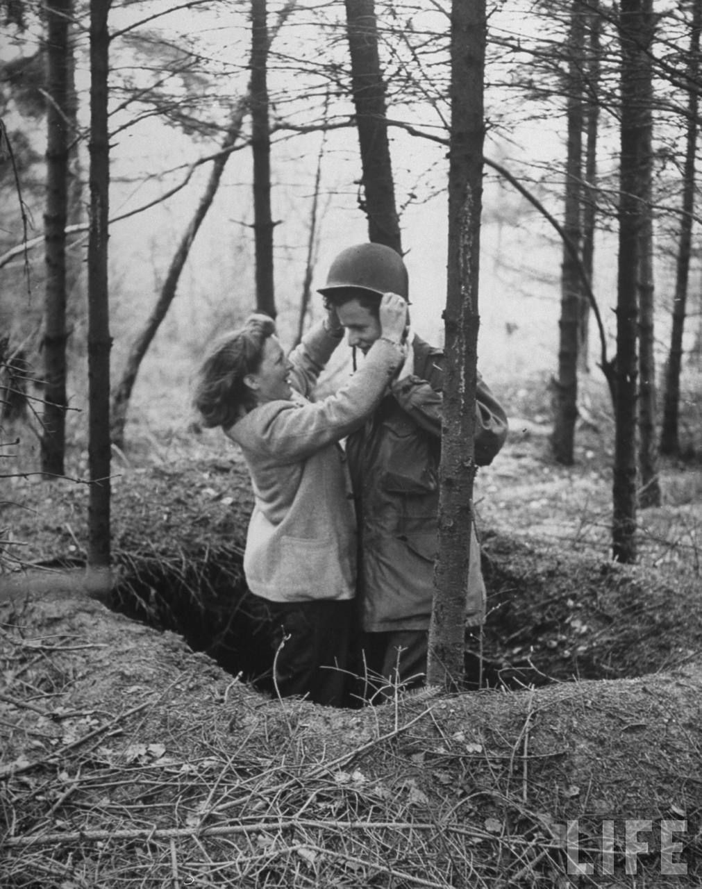 Ex-Sgt. Ernie Kreiling gets helmet put on his head by his laughing wife in the foxhole where he first heard an enemy shell during their vacation tour of battlefields were he fought during WWII in North country France - April 1947