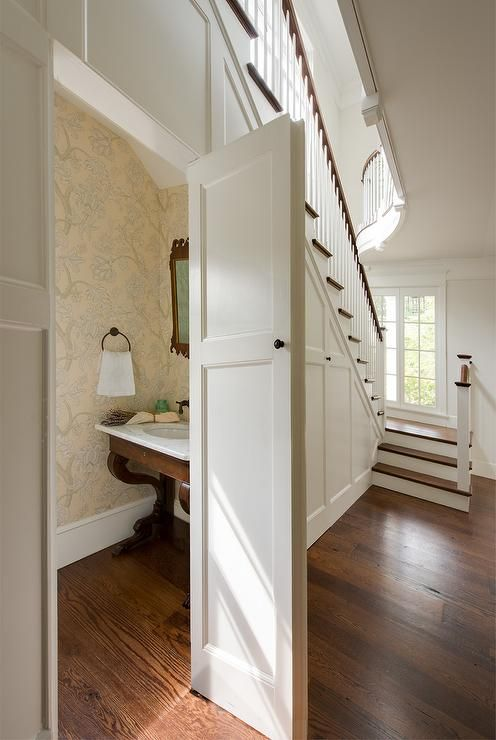 Best Hidden Powder Room Under The Stairs Is Filled With A Wood And Marble Washstand Under A Carv 400 x 300