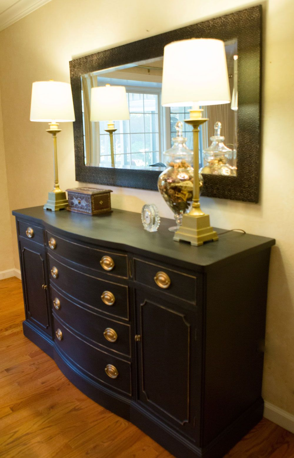 Black Gold Buffet Accessorized With Tall Table Lamps Bases And A Large Mirror Framed In Hammered Metal