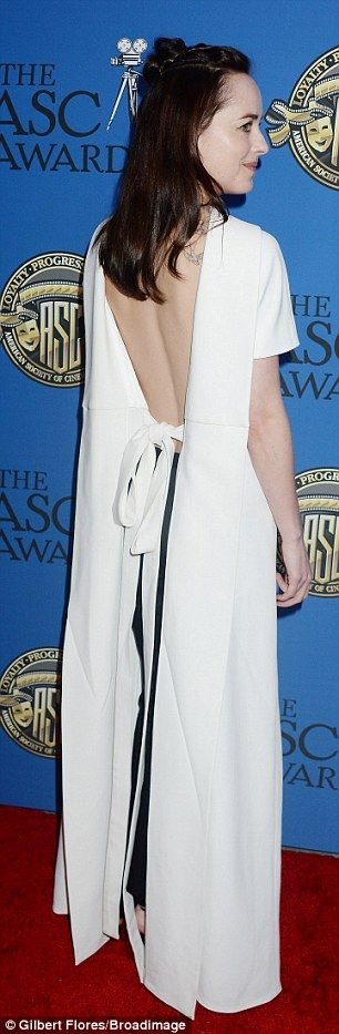 MIxing it up: Dakota turned around to reveal her back on show in the short sleeved garment which was layered over slim-fit black pants
