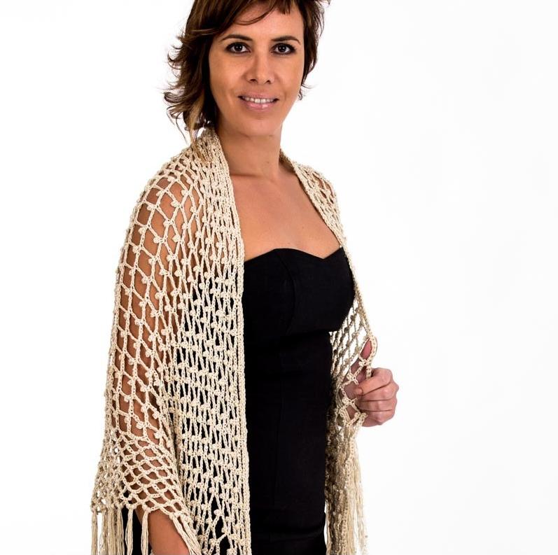 Chal elaborado artesanalmente con hilo sintético tejido a crochet con la técnica de malla en forma de arcos y decorado con lentejuelas entrelazadas.