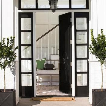 Chic Home Features A Glossy Black Front Door With Black 5 Panel Sidelights  And Transom Window Illuminated By A Black Lantern Flanked By Potted Plants  In ...