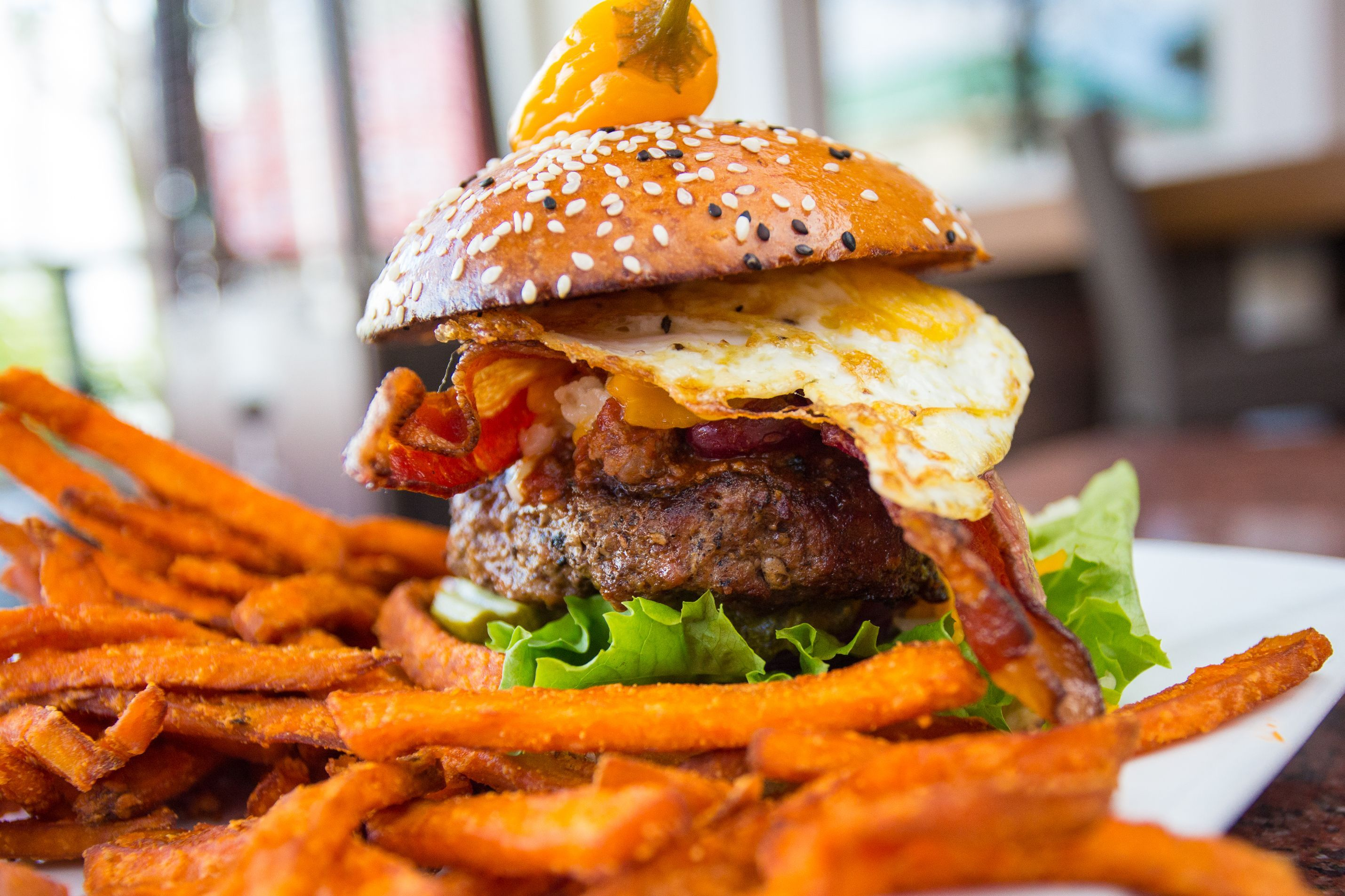 The Hangover Burger: a 7-oz. burger with chili, bacon, jack and cheddar cheese, caramelized onions and a sunny-side egg. Topped with a habanero pepper