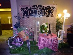 Paris themed corporate holiday party. Cafe set up with bistro tables and floral arrangements.