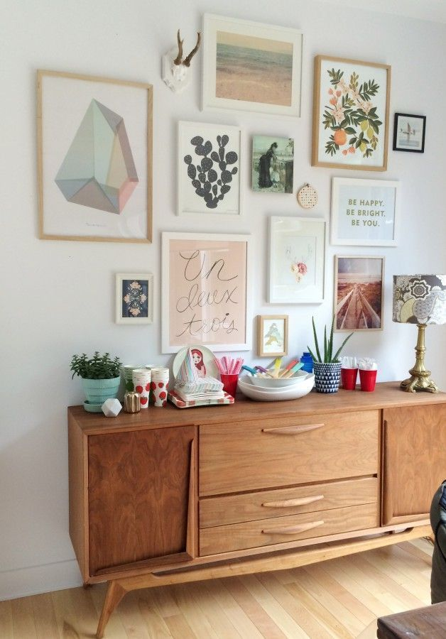 Love this gallery wall with cool colors and mid century furniture this is so pretty